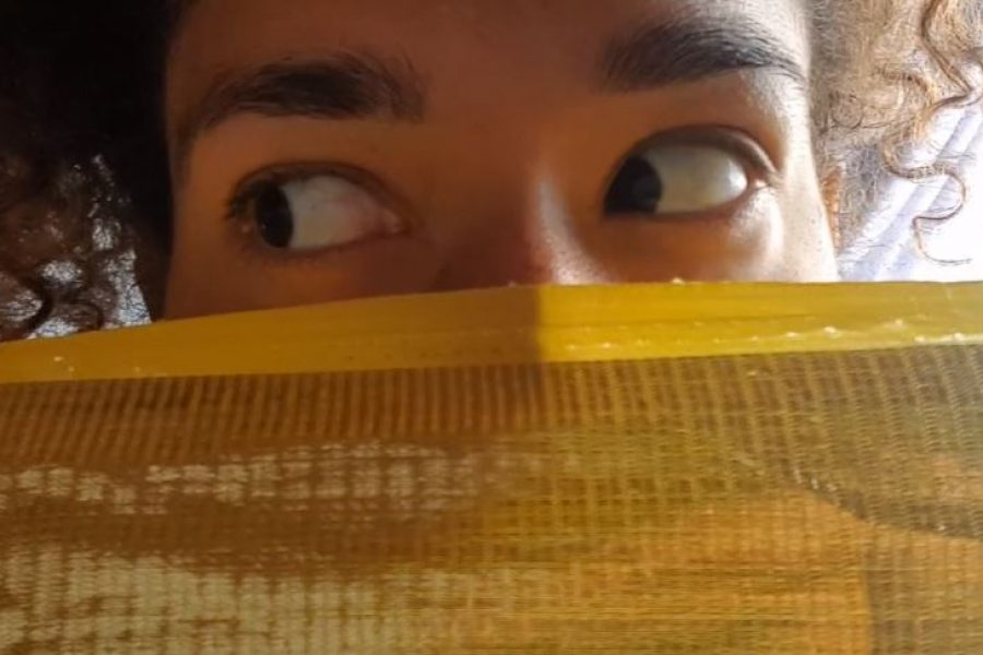 a womens eyes with face covered by gold cloth