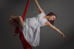 Woman suspended on a red cloth acobatically poised