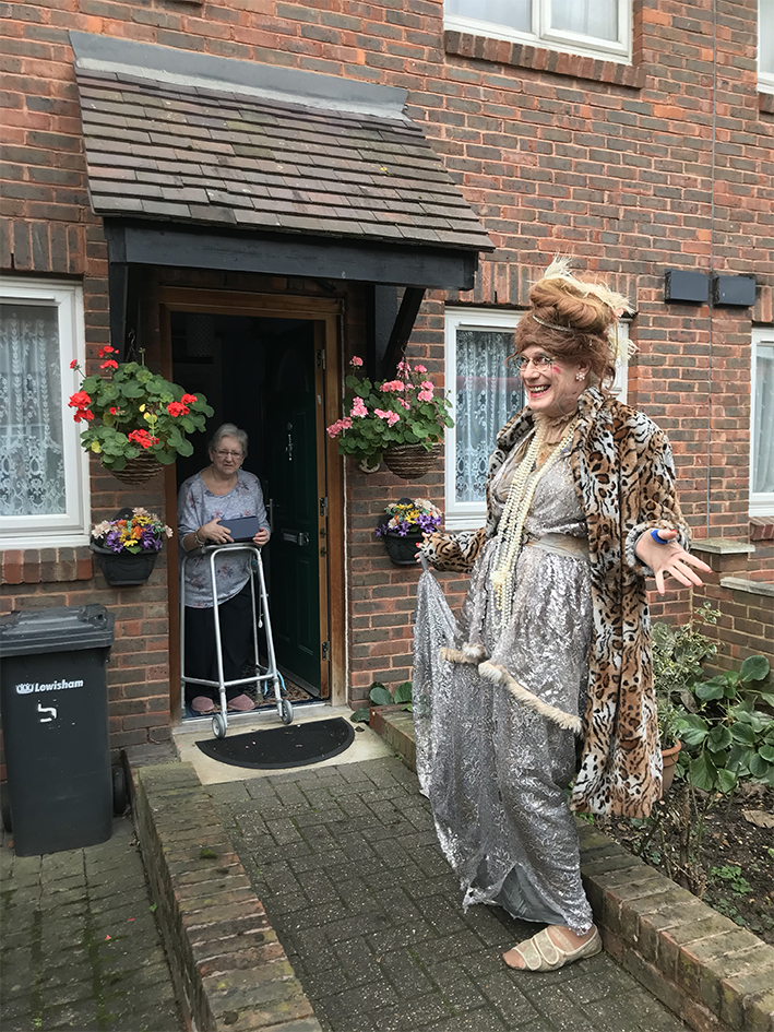 man dressed up as a woman visitng a doorstep of elderly person for fun