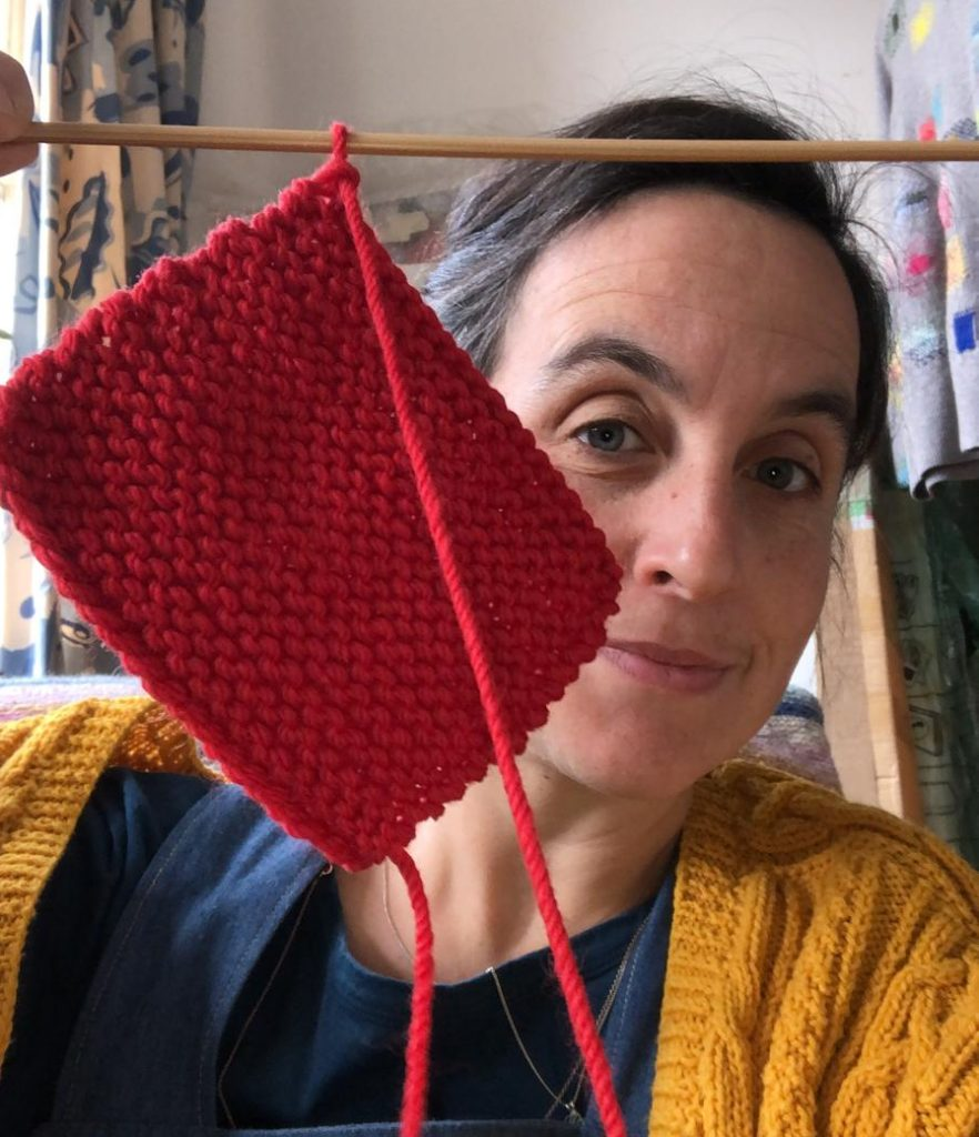 image of an artist holding up her red knitting
