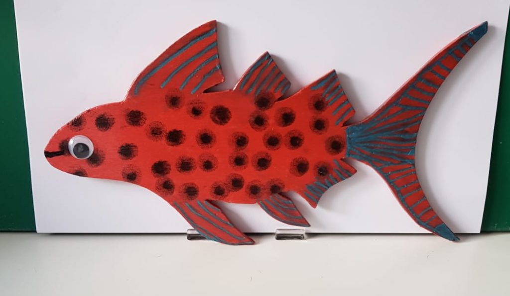 a fish made of wood and painted in bright colours
