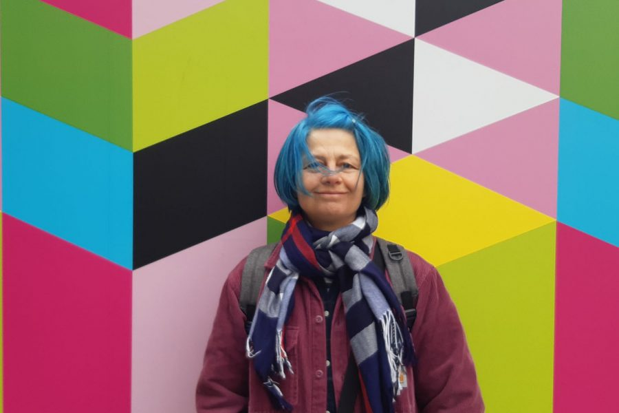 Portrait of Christine against a bright pattern background