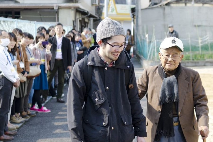 one older and one younger japanese men walking along a path with people gathered in a line watching them.