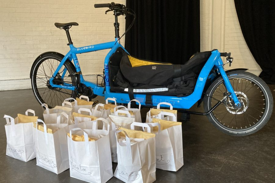 A blue bicycle that can carry cargo with packages in neat rows next to it.
