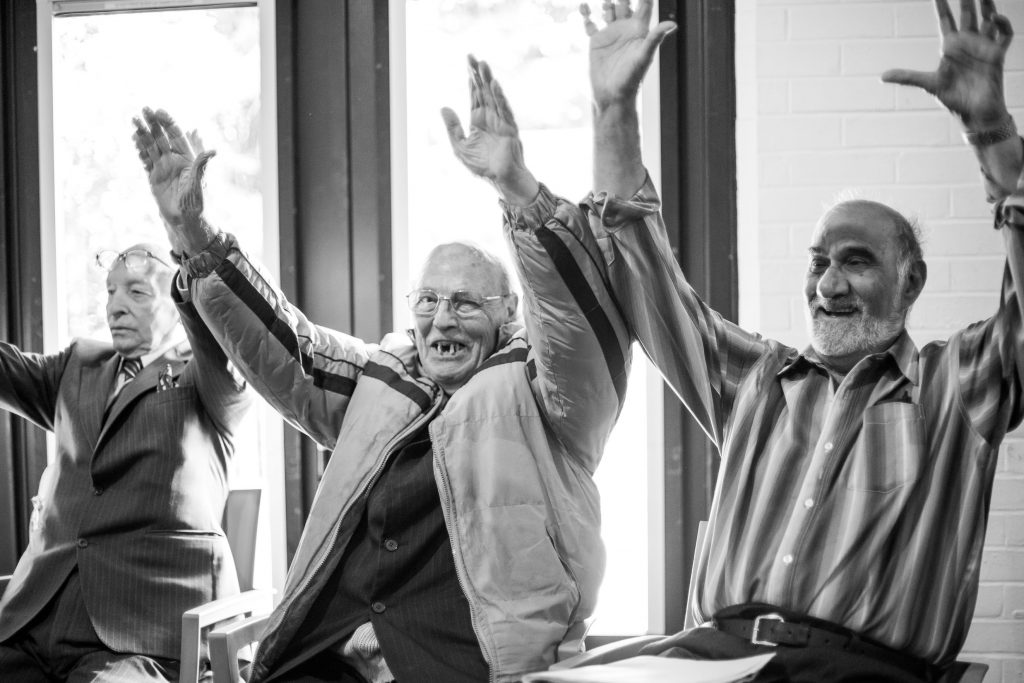 three older men smiling with their arms raised in the air.