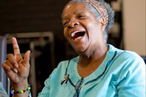 portrait of a smiling black woman in turquoise cardigan with a head scarf.
