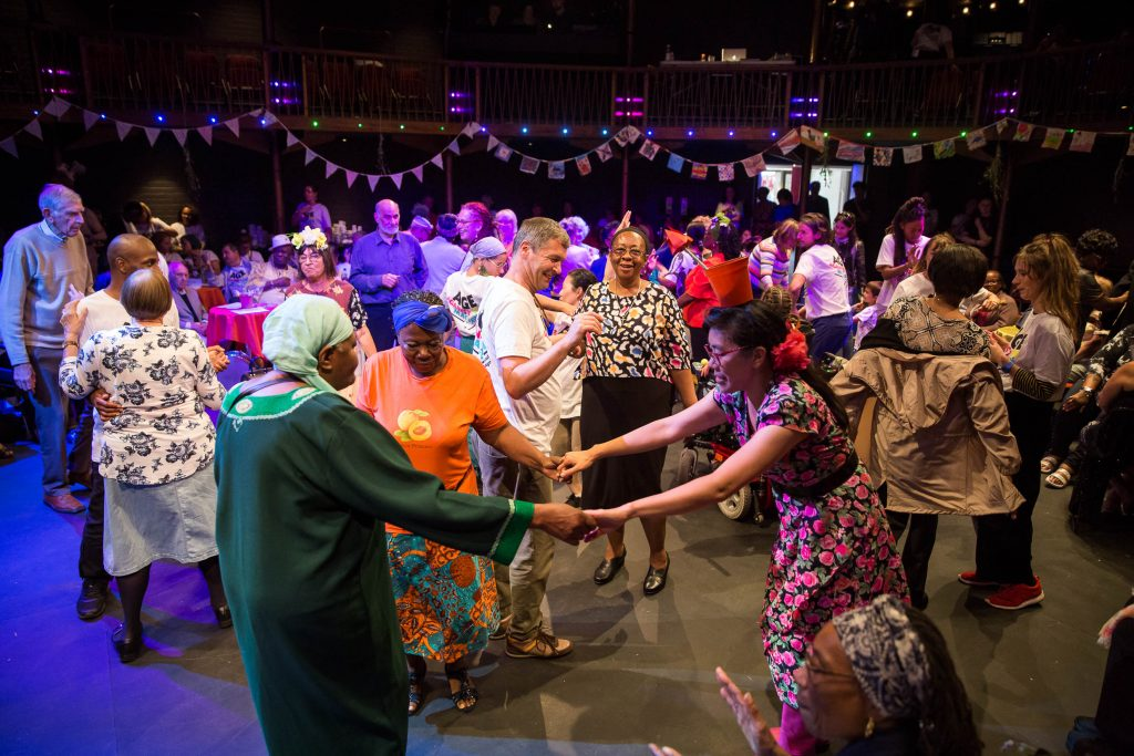 Many people in a hall dressed up and dancing together