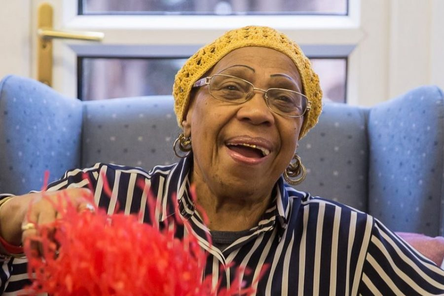 black woman laughing wearing a yellow knitted hat