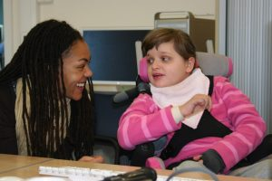 black woman talking to girl in a wheelchair