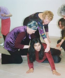 a women crouched on the floor being looked at and moved by 5 people