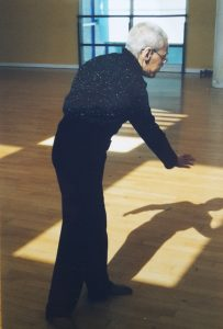 an older woman dancing with her back to the camera