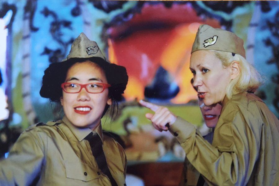 two women dressed in military uniforms outside a tent