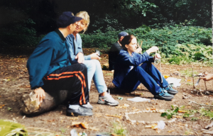 four people sitting ina wood on a log talking