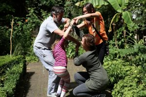 3 adults and a child playing together in a garden