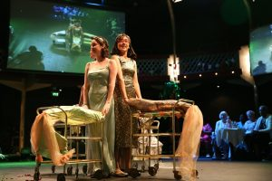 two women dressed in costume performing a dance with trolleys to an audience