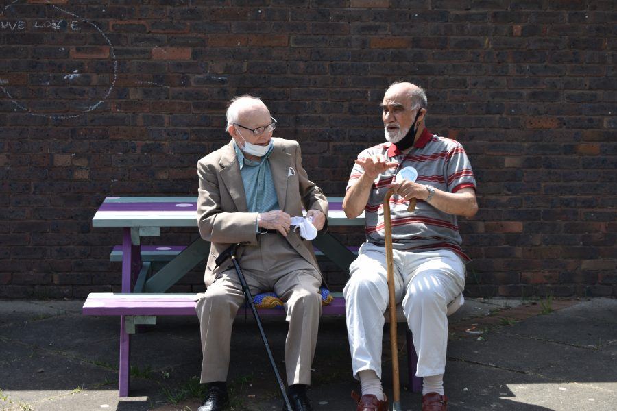 Two older men chatting on a bench.