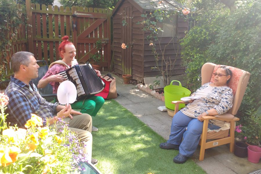 Two men and a woman sitting in a garden. One of the man is playing the accordion.