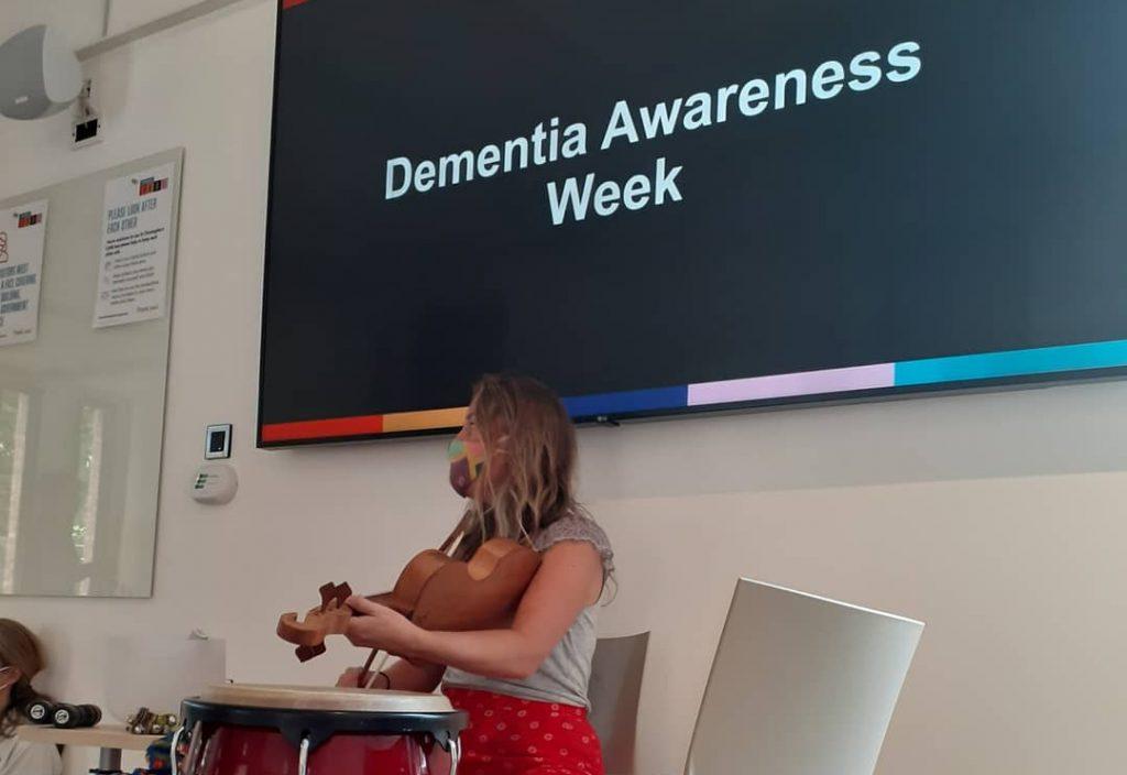 A blonde woman plays the violin. Behind her a screen read Dementia Awareness Week.
