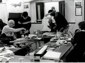 Black and white photo of a group of older people sitting a tables full of arts and craft material. Two volunteers help them handling the material.