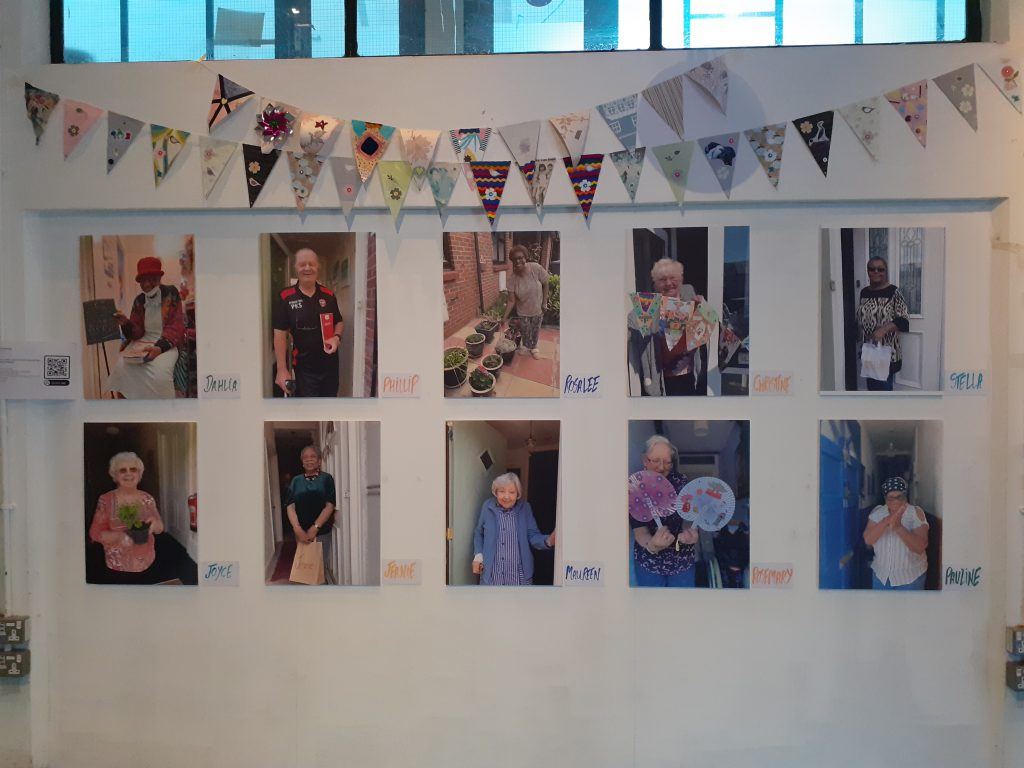 A white wall with photos of older people and colourful bunting hanging at the top